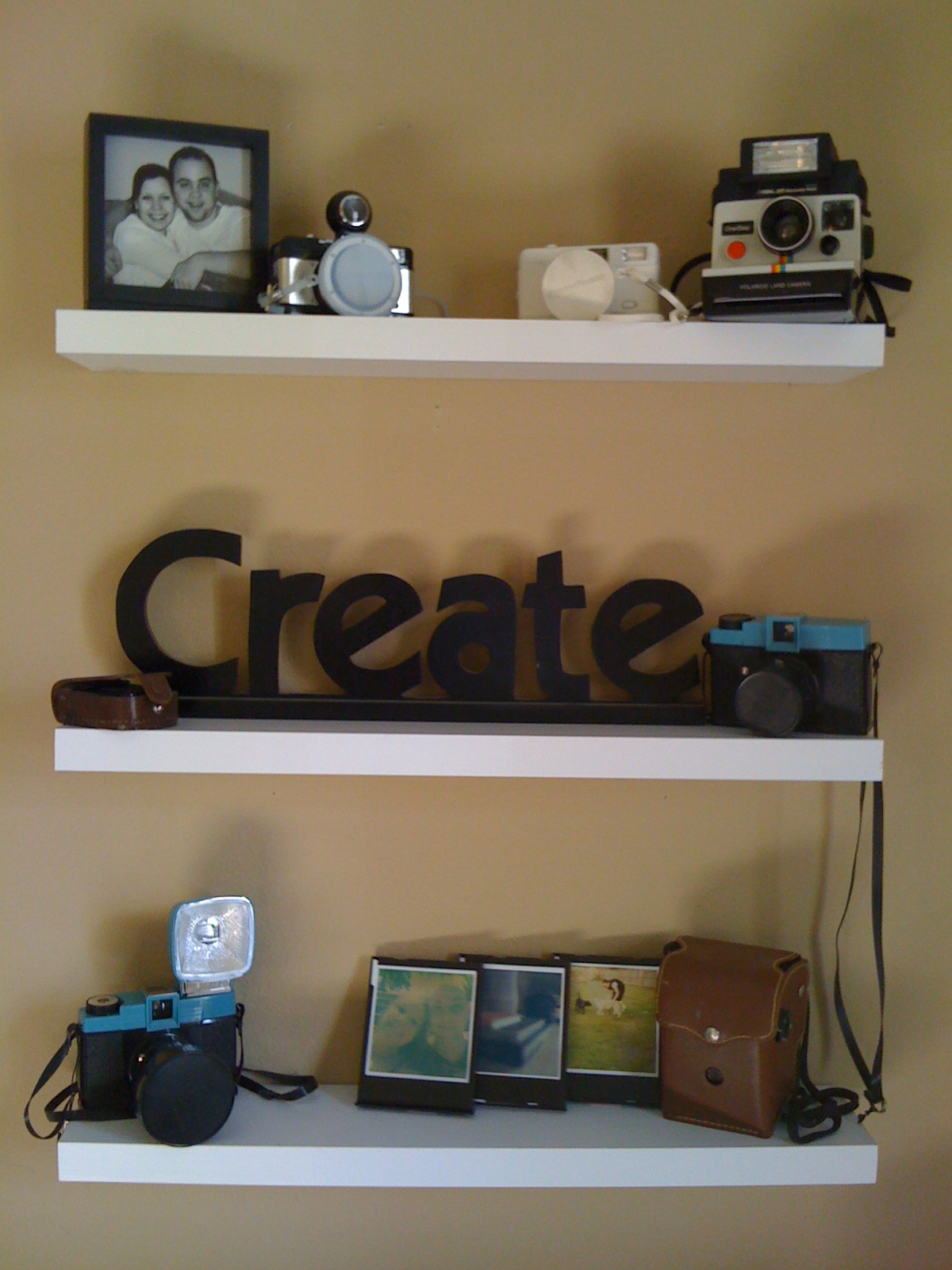 White shelves with vintage cameras and Polaroids